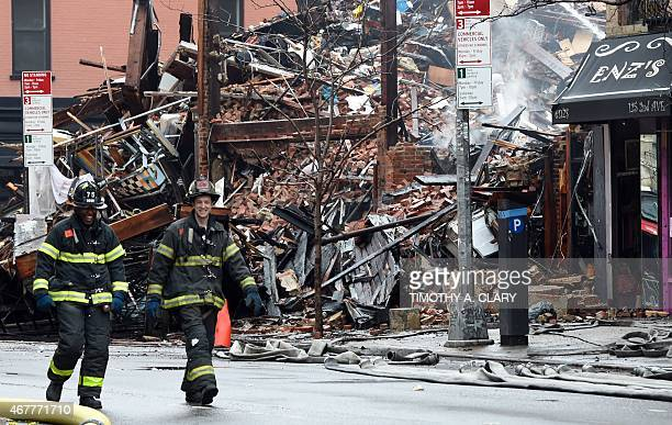 New York City Fire Department firefighters walk by debris the morning after the fire at the commercial and residential block on March 27 in New...