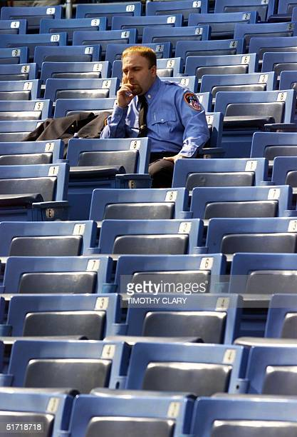New York City firefighter sits quietly alone in the stands while he awaits the start of the 'Prayer For America' memorial service at New York's...