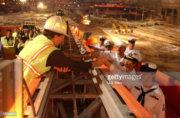 New York City firefighters and recovery workers exchange handshakes at 'Ground Zero' as US Navy Sailors visit May 28 2002 in New York City during the...