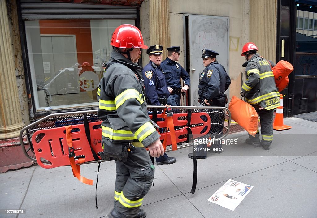 New York City firefighters enter a site April 30, 2013 in Lower Manhattan where New York police said that they have found a fragment of one of two airplanes that slammed into the World Trade Center on September 11, 2001. The fragment was found April 27 and the medical examiner will be searching for possible human remains before the part of the plane is removed. AFP PHOTO/Stan HONDA