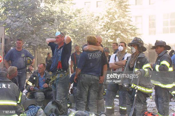 New York City firefighters hug each other during rescue operations at the World Trade Center after two hijacked planes crashed into the Twin Towers...