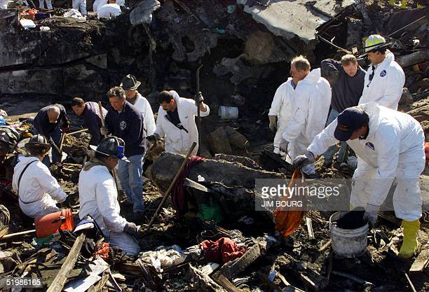 New York City firefighters in protective gear retrieve evidence clothing and human remains from the pit 14 Novewmber 2001 at the corner of Beach...