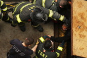 New York City firefighters use an emergency staircase to evacuate passengers from a derailed F train on May 2 2014 in the Woodside neighborhood of...