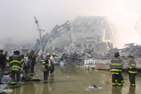 New York City firefighters work at the World Trade Center after two hijacked planes crashed into the Twin Towers September 11 2001 in New York