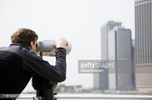 USA, New York City, Manhattan, man looking at skyline through telescope