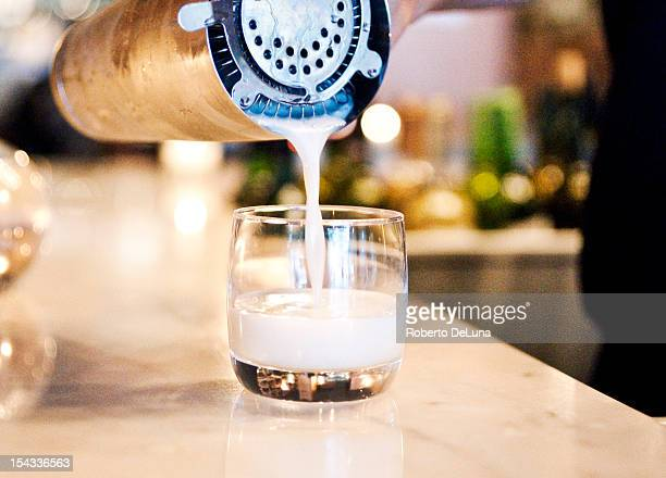 USA, New York City, Manhattan, pouring pisco sour from shaker to glass