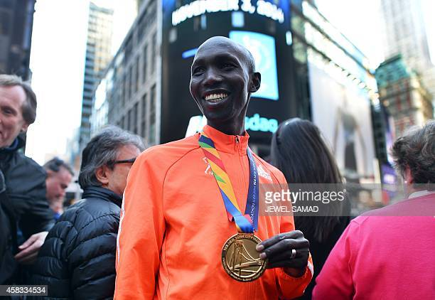 New York City Marathon men's winner Kenyan Wilson Kipsang smiles as he poses with tourists in Times Square in New York on November 3 2014 Kipsang...