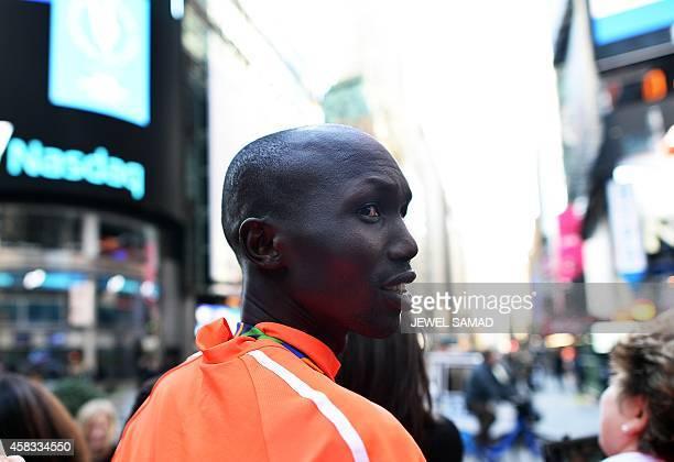 New York City Marathon men's winner Kenyans Wilson Kipsang smiles as he poses with tourists in Times Square in New York on November 3 2014 Kipsang...