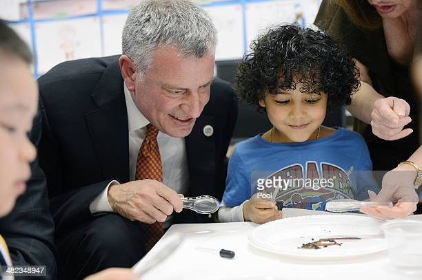 New York City Mayor Bill de Blasio and student Justin De La Cruz work on a science project with worms during a visit to a preK classroom at PS1 on...
