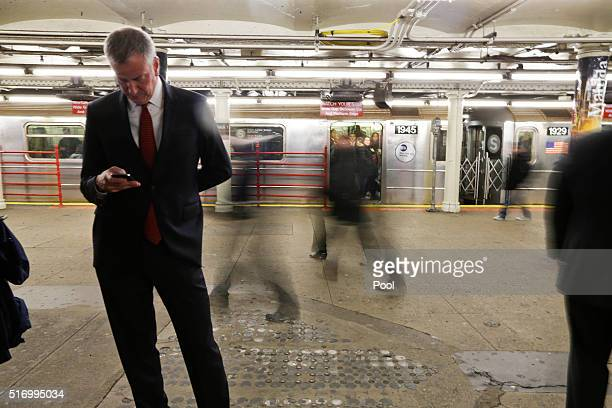 New York City Mayor Bill de Blasio checks his phone as patrons ride the subway March 22 2016 in New York City Security was tightened in New York...