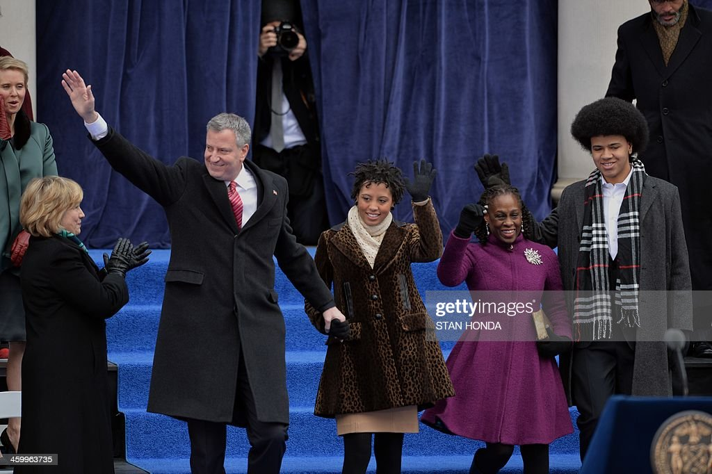 New York City Mayor Bill de Blasio (L), daughter Chiara (2nd L), wife Chirlane (2nd R) and son Dante (R) wave from the steps of City Hall in Lower Manhattan on January 1, 2014 in New York. Democrat de Blasio is sworn in as mayor of New York in a ceremony on the steps of city hall overseen by former US President Bill Clinton. De Blasio, pledging to alleviate growing inequality and improve public services, succeeds billionaire Michael Bloomberg. AFP PHOTO/Stan HONDA