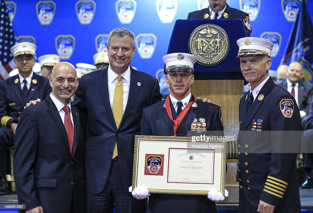 New York City Mayor Bill de Blasio (2ndL), FDNY Fire chief Edward S. Kilduff (R) and FDNY Commissioner Salvatore Cassano (L) pose with firefighter James P. Ellson (2ndR), 2014 FDNY Medal Day Recipient, for his exceptional acts of valor at the New York State Armory in Manhattan on June 4, 2014. The firefighters were honored for their heroic actions in the line of duty.