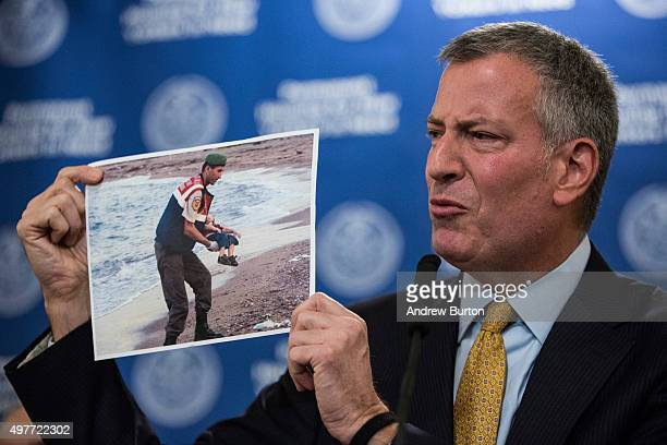 New York City Mayor Bill de Blasio holds up a photo of a the body of a dead child refugee being recovered from a beach while criticizing New Jersey...