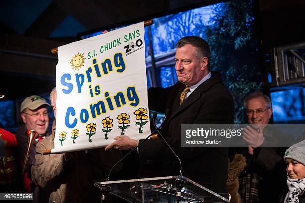 New York City Mayor Bill de Blasio holds up a sign announcing spring is here as he speaks at a Groundhogs Day event after viewing Staten Island Chuck...