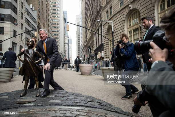 New York City Mayor Bill De Blasio poses for a photo with the 'Fearless Girl' statue during a press availability March 27 2017 in New York City De...