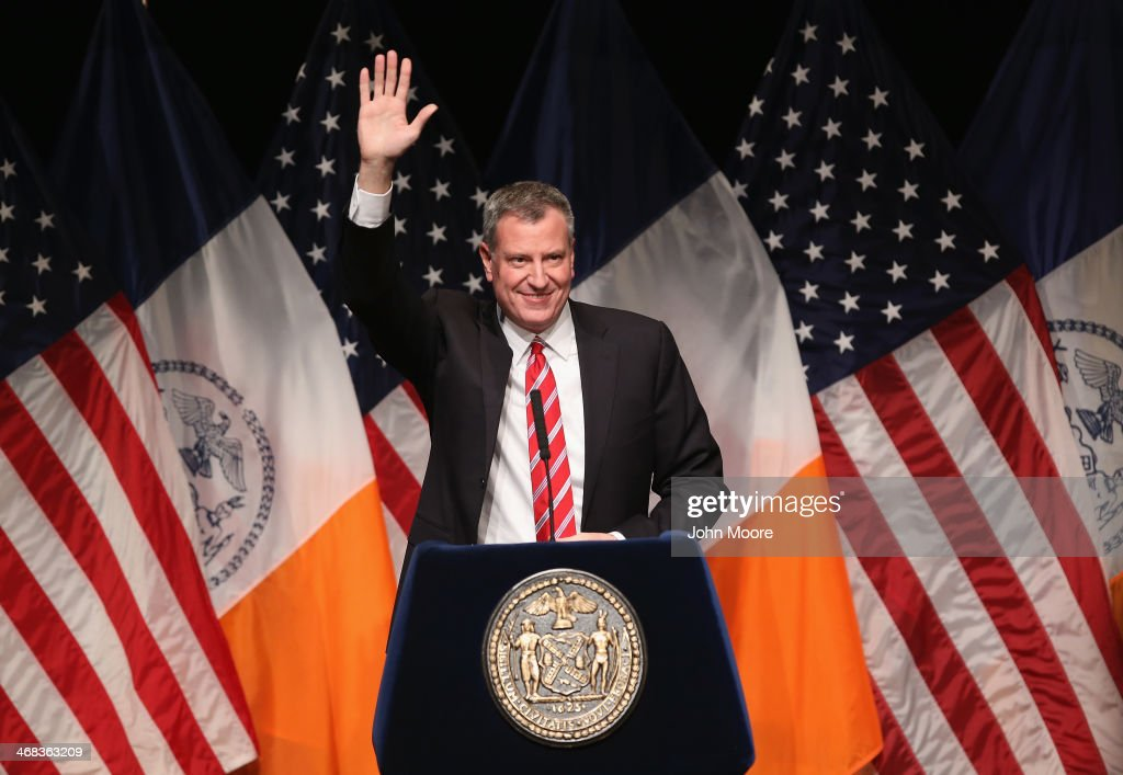 New York City Mayor <a gi-track='captionPersonalityLinkClicked' href=/galleries/search?phrase=Bill+de+Blasio&family=editorial&specificpeople=6224514 ng-click='$event.stopPropagation()'>Bill de Blasio</a> waves as he gives the State of the City address at La Guardia Community College on February 10, 2014 in the Long Island City section of the Queens borough of New York City. In his first address as Mayor of New York de Blasio plans to outline his vision for fighting the widening income inequality gap and intends to urge lawmakers to raise the minimum wage.