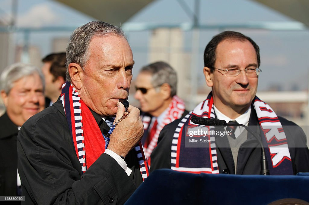 New York City Mayor Michael Bloomberg (L) blows a whistle to officially open Brooklyn Bridge Park - Pier 5 as New York Red Bulls General Manager Jerome de Bontin looks on during a ribbon-cutting ceremony at Brooklyn Bridge Park on December 13, 2012 in New York City.
