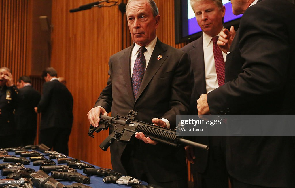 New York City Mayor Michael Bloomberg (C) displays a confiscated AR-15 assault rifle above a table of illegal firearms sold to undercover officers in a large weapons bust in East Harlem as District Attorney Cy Vance (R) looks on during a press conference on October 12, 2012 in New York City. NYPD detectives arrested 13 suspects for the illegal sale of 129 guns mostly purchased from gun dealers and pawn shops in South Carolina.