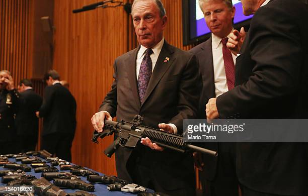 New York City Mayor Michael Bloomberg displays a confiscated AR15 assault rifle above a table of illegal firearms sold to undercover officers in a...