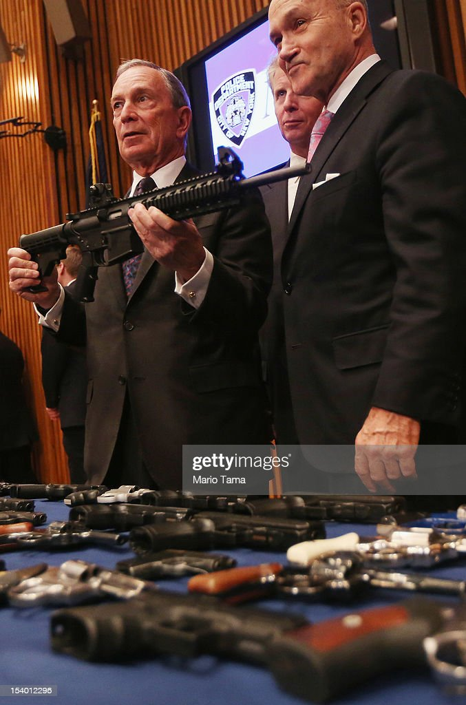 New York City Mayor Michael Bloomberg holds a confiscated AR-15 assault rifle as District Attorney Cy Vance and Police Commissioner Ray Kelly stand above a table of illegal firearms sold to undercover officers in a large weapons bust in East Harlem during a press conference on October 12, 2012 in New York City. NYPD detectives arrested 13 suspects for the illegal sale of 129 guns mostly purchased from gun dealers and pawn shops in South Carolina.