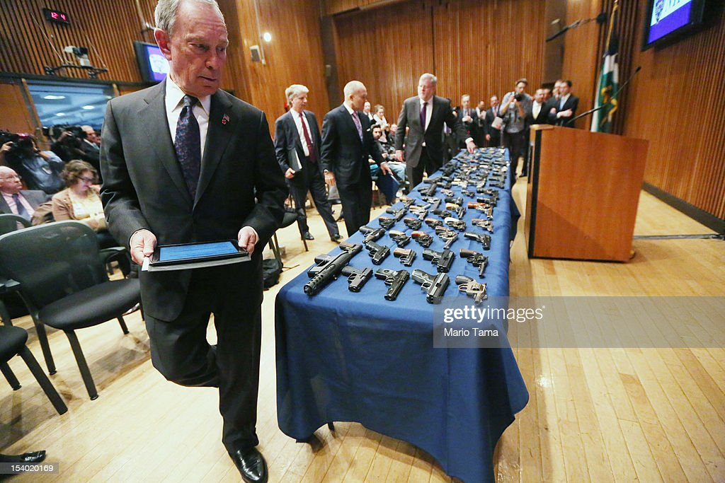 New York City Mayor Michael Bloomberg (LEFT) walks around a table of illegal firearms sold to undercover officers in a large weapons bust in East Harlem at the start of a press conference on October 12, 2012 in New York City. NYPD detectives arrested 13 suspects for the illegal sale of 129 guns mostly purchased from gun dealers and pawn shops in South Carolina.
