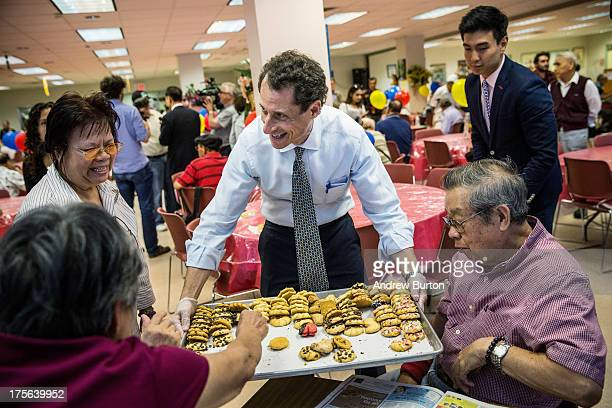 New York City mayoral candidate and former US Rep Anthony Weiner hands out cookies to seniors at Elmhurst Senior Center on August 5 2013 in New York...