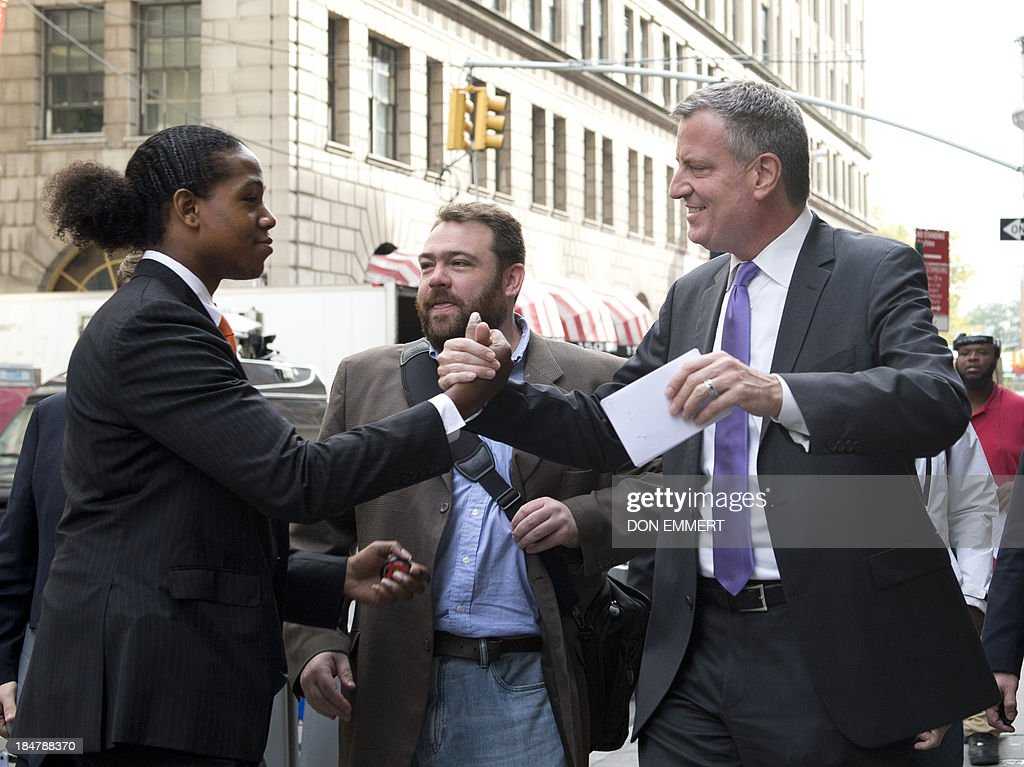 New York City mayoral candidate Bill De Blasio (R) greets a supporter near a Burger King on October 16, 2013 in New York. De Blasio says low-wage fast food jobs are a cost to New York State taxpayers. He states that new research fromthe University of California, Berkeley, shows how low-wage, no-benefit fast food jobs force workers to rely on public assistance programs, leaving taxpayers to foot the bill. AFP PHOTO/Don Emmert