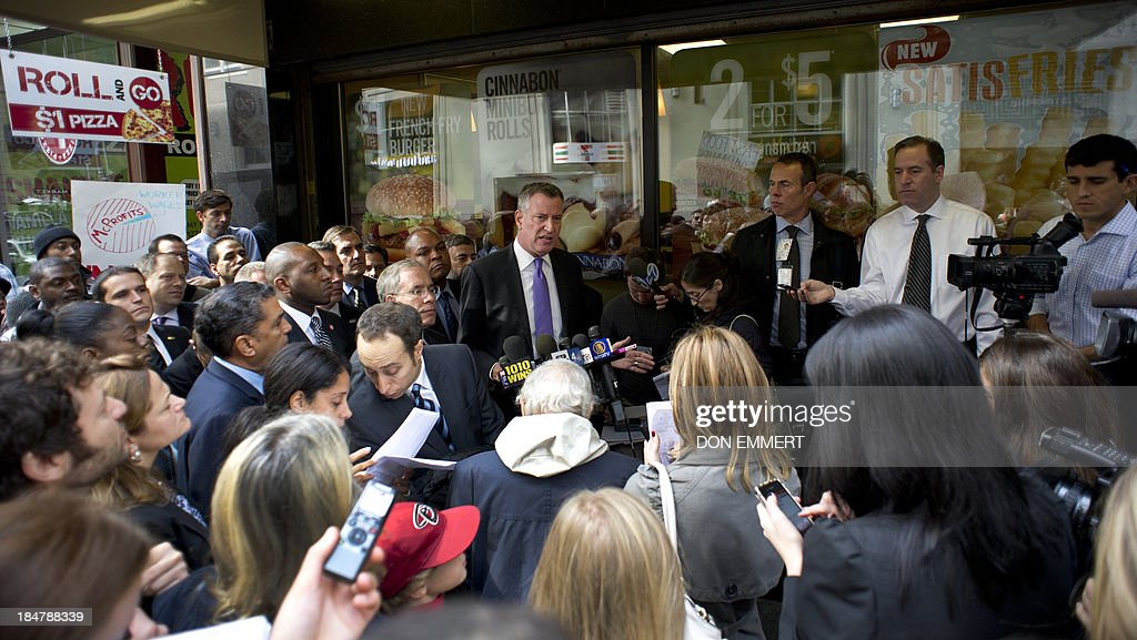New York City mayoral candidate Bill De Blasio talks to supporters outside a Burger King on October 16, 2013 in New York. De Blasio says low-wage fast food jobs are a cost to New York State taxpayers. He states that new research fromthe University of California, Berkeley, shows how low-wage, no-benefit fast food jobs force workers to rely on public assistance programs, leaving taxpayers to foot the bill. AFP PHOTO/Don Emmert