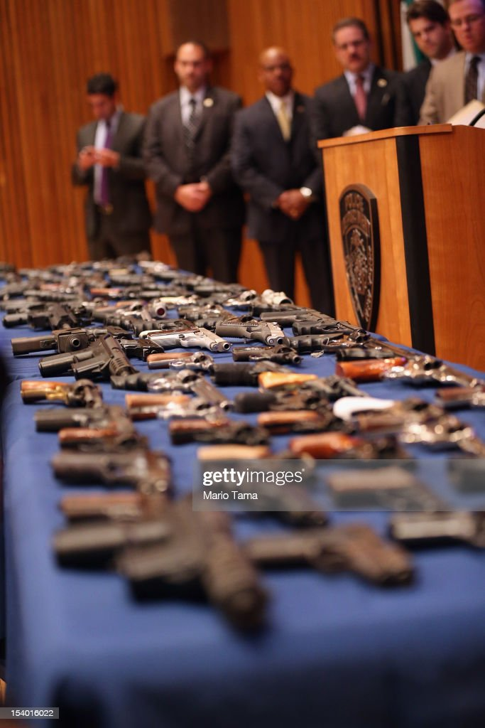 New York City officials stand above a table of illegal firearms sold to undercover officers in a large weapons bust in East Harlem during a press conference on October 12, 2012 in New York City. NYPD detectives arrested 13 suspects for the illegal sale of 129 guns mostly purchased from gun dealers and pawn shops in South Carolina.