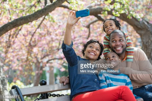 A New York city park in the spring. Cherry blossom. A woman taking a selfy picture with her smart phone of her family. : Stock Photo