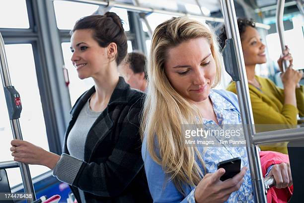 New York City park. People, men and women on a city bus. Public transport. Keeping in touch. A young woman checking or using her cell phone.