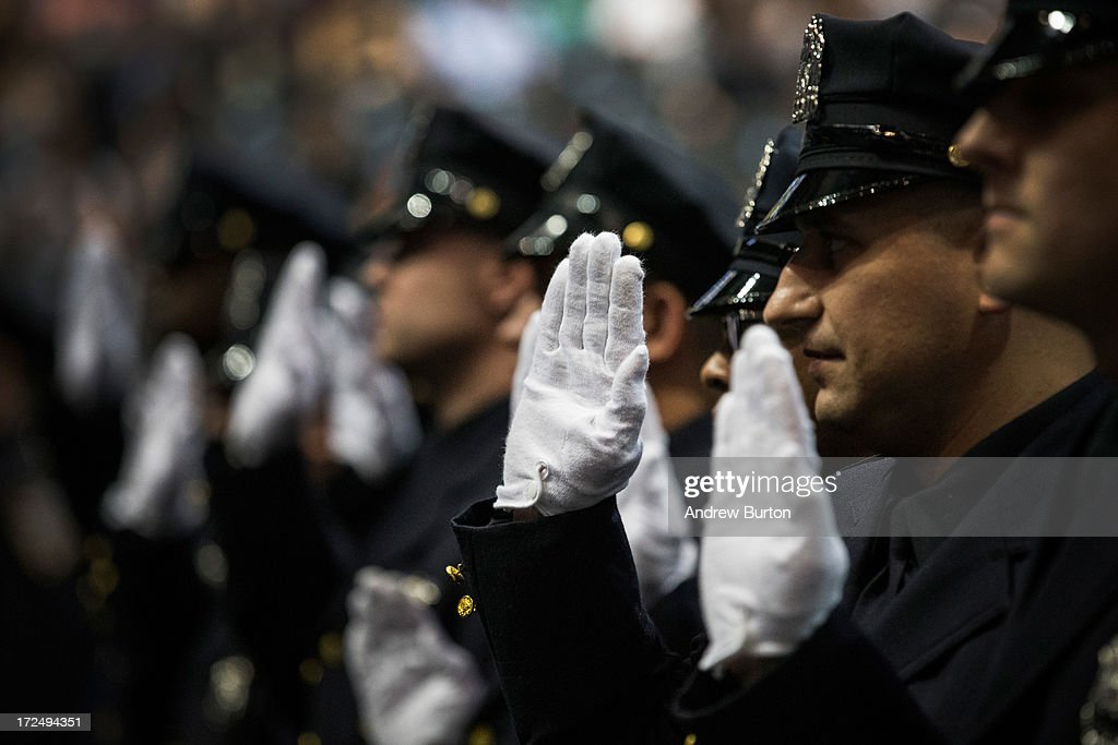 New York City Police Academy cadets raise their hand during their graduation ceremony at the Barclays Center on July 2, 2013 in the Brooklyn borough of New York City. The New York Police Department (NYPD) has more than 37,000 officers; 781 cadets graduated today.