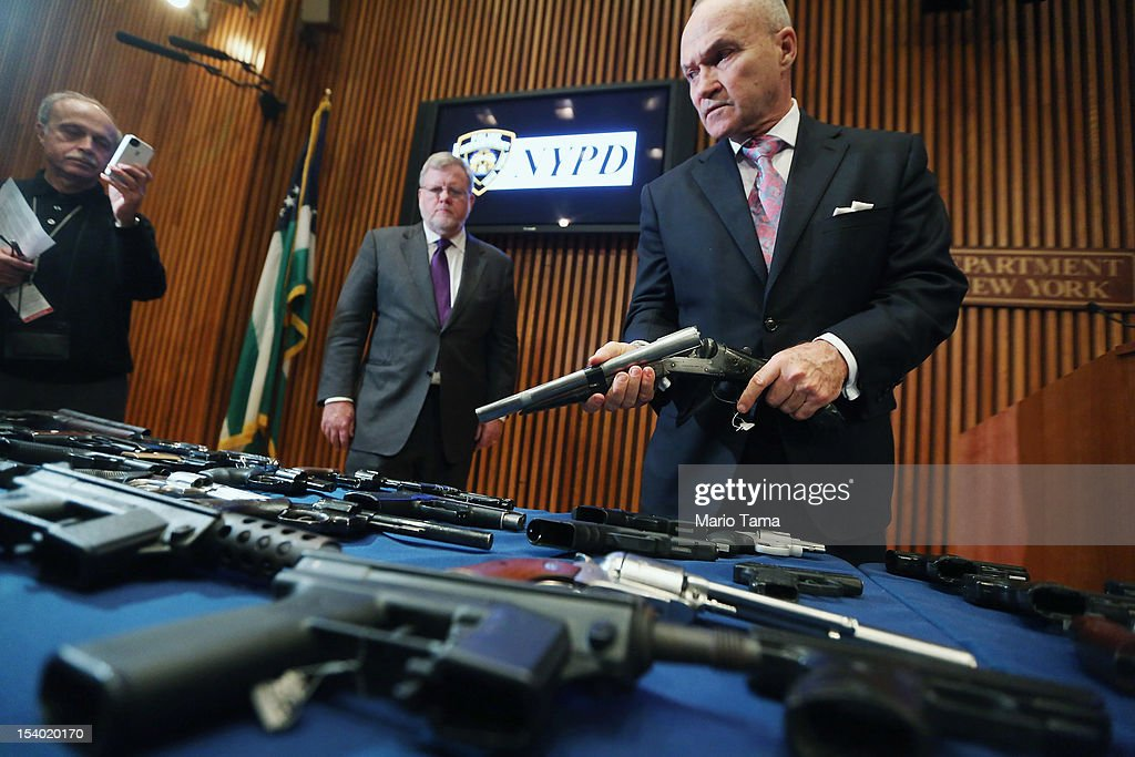 New York City Police Commissioner Ray Kelly (R) holds a confiscated gun above a table of illegal firearms sold to undercover officers in a large weapons bust in East Harlem during a press conference on October 12, 2012 in New York City. NYPD detectives arrested 13 suspects for the illegal sale of 129 guns mostly purchased from gun dealers and pawn shops in South Carolina.