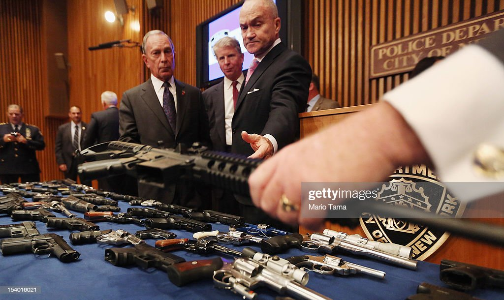 New York City Police Commissioner Ray Kelly (R) is handed a confiscated AR-15 assault rifle above a table of illegal firearms sold to undercover officers in a large weapons bust in East Harlem as Mayor Michael Bloomberg (3R) and District Attorney Cy Vance (2R) look on during a press conference on October 12, 2012 in New York City. NYPD detectives arrested 13 suspects for the illegal sale of 129 guns mostly purchased from gun dealers and pawn shops in South Carolina.