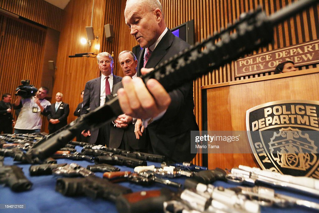 New York City Police Commissioner Ray Kelly (C) lifts a confiscated AR-15 assault rifle above a table of illegal firearms sold to undercover officers in a large weapons bust in East Harlem as Mayor Michael Bloomberg (C LEFT) and District Attorney Cy Vance look on during a press conference on October 12, 2012 in New York City. NYPD detectives arrested 13 suspects for the illegal sale of 129 guns mostly purchased from gun dealers and pawn shops in South Carolina.