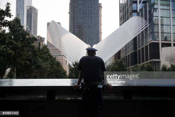 New York City Police Department officer pauses while visiting the North pool during a commemoration ceremony for the victims of the September 11...
