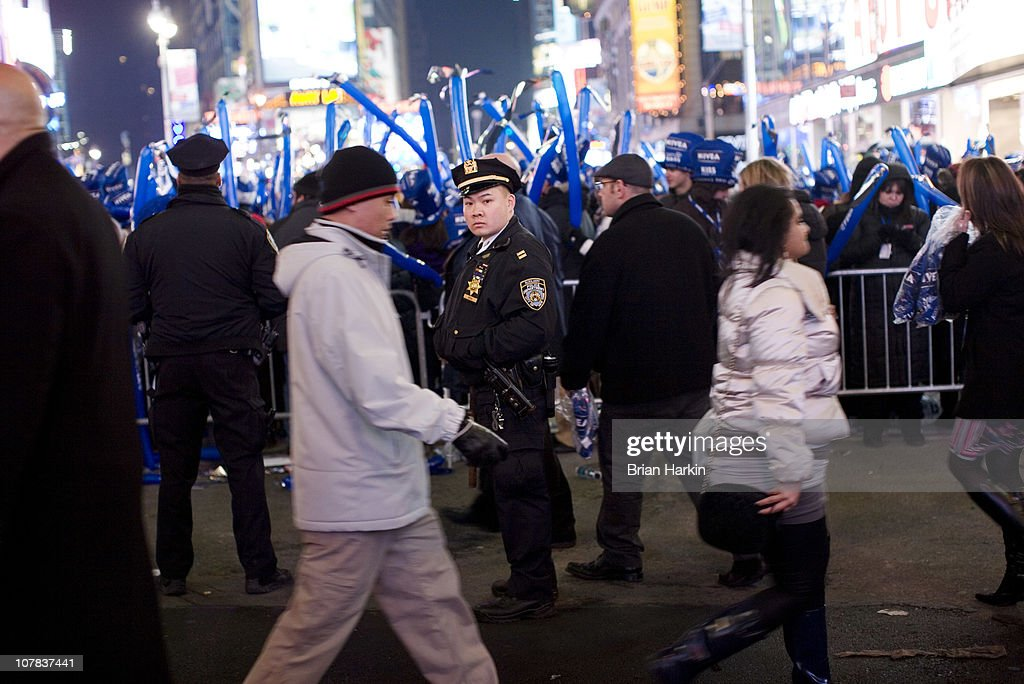 A New York City Police Department officer watches the crowd in Times Square hours before the annual ball drop December 31, 2010 in New York City. The police department sets up corrals for the revelers which allows others to flow between the barricades.