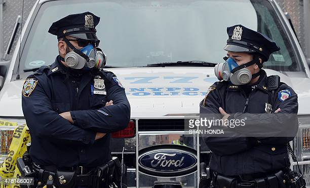 New York City Police Department officers wear masks at the scene of an explosion and building collapse at Park Avenue and East 116th Street March 12...