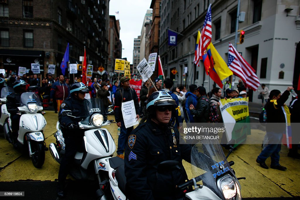 New York City police keep an eye on demonstrators participating in a May Day rally on May 1, 2016 in New York. May Day has shared a date with International Workers' Day since the 1880s. At the time, labor movements around the world were fighting for fair work accommodations like eight-hour workdays and unions. / AFP / KENA