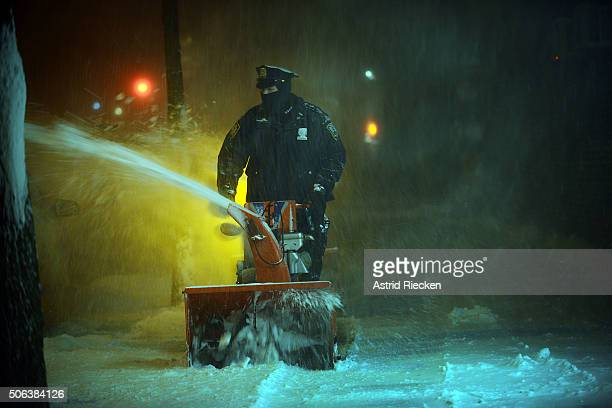 New York City police office of the 20th District use snow blowers to clean the sidewalks at West 81st street on January 23 2016 in New York City A...