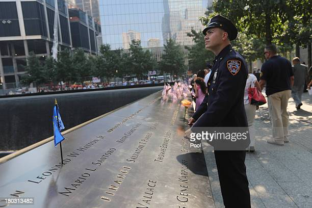 New York City police officer pays his respects at the South Pool of the 9/11 Memorial during ceremonies for the twelfth anniversary of the terrorist...