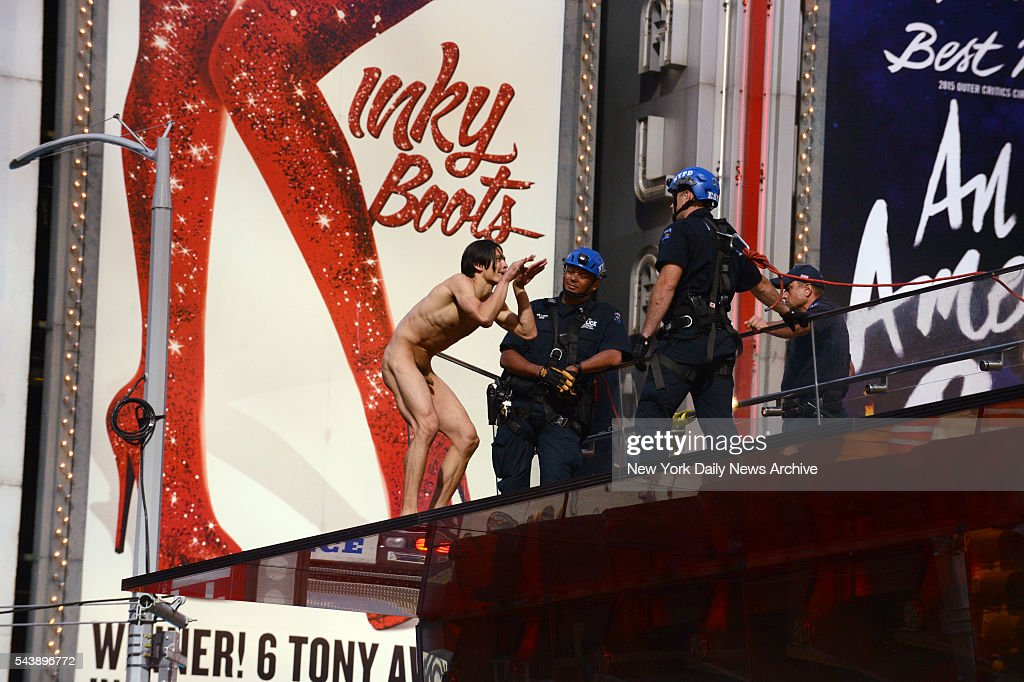 New York City police officers confront an unidentified naked man screaming about Donald Trump above New York's Times Square on Thursday, June 30, 2016. He was injured after falling off the red steps at the TKTS booth as scores of people - including cops - looked on in disbelief.