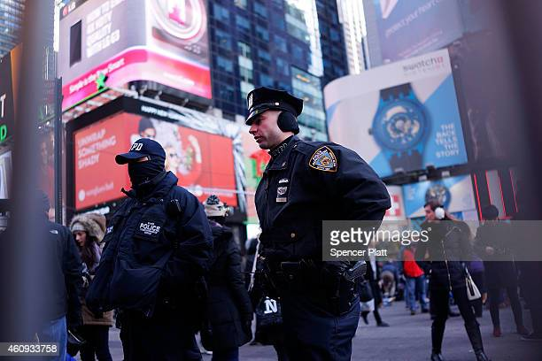 New York City police officers stand guard in Times Square on December 31 2014 in New York City An estimated one million people from around the world...