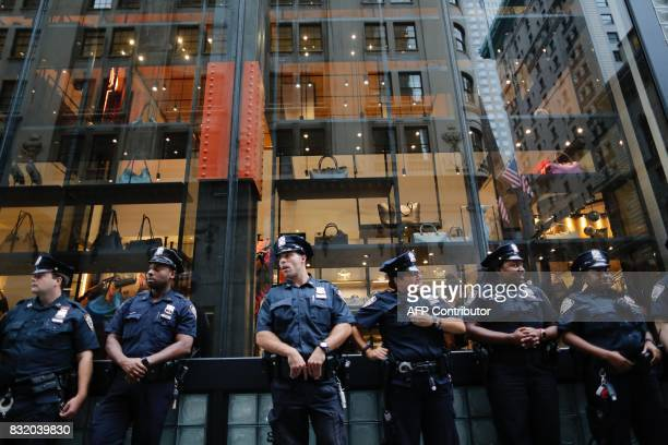 New York City police officers stand guard near Trump Tower during protests against attacks on immigrants under policies of US President Donald Trump...