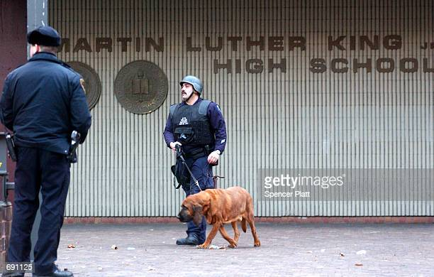 New York City Police officers stand guard outisde Martin Luther King Jr High School after two students were wounded in a shooting in the school...