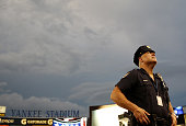New York City police officers stand on the field during a rain delay before the game between the Boston Red Sox and New York Yankees at Yankee...