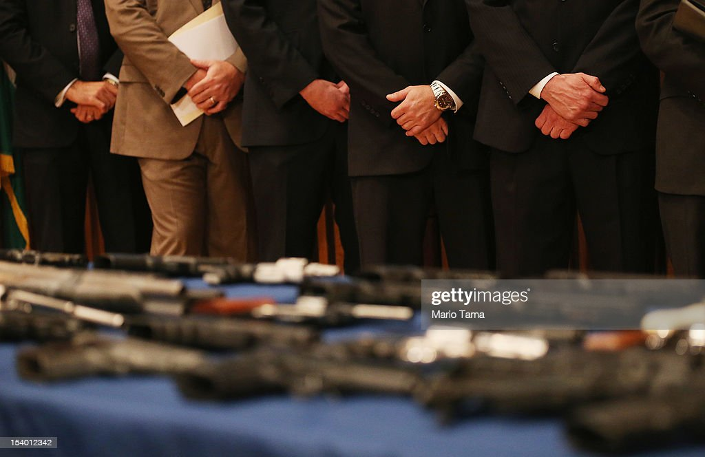 New York City Police officials stand above a table of illegal firearms sold to undercover officers in a large weapons bust in East Harlem during a press conference on October 12, 2012 in New York City. NYPD detectives arrested 13 suspects for the illegal sale of 129 guns mostly purchased from gun dealers and pawn shops in South Carolina.