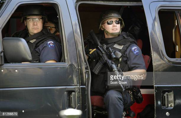 New York City police stand guard with automatic weapons outside the entrance of the Church of Our Saviour Catholic church while President George Bush...