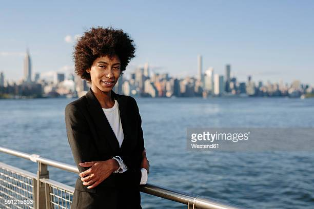 USA, New York City, portrait of businesswoman in front of skyline