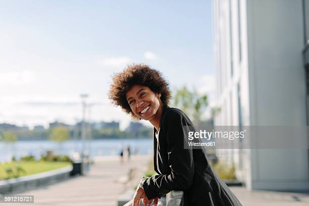 USA, New York City, portrait of smiling businesswoman leaning on railing